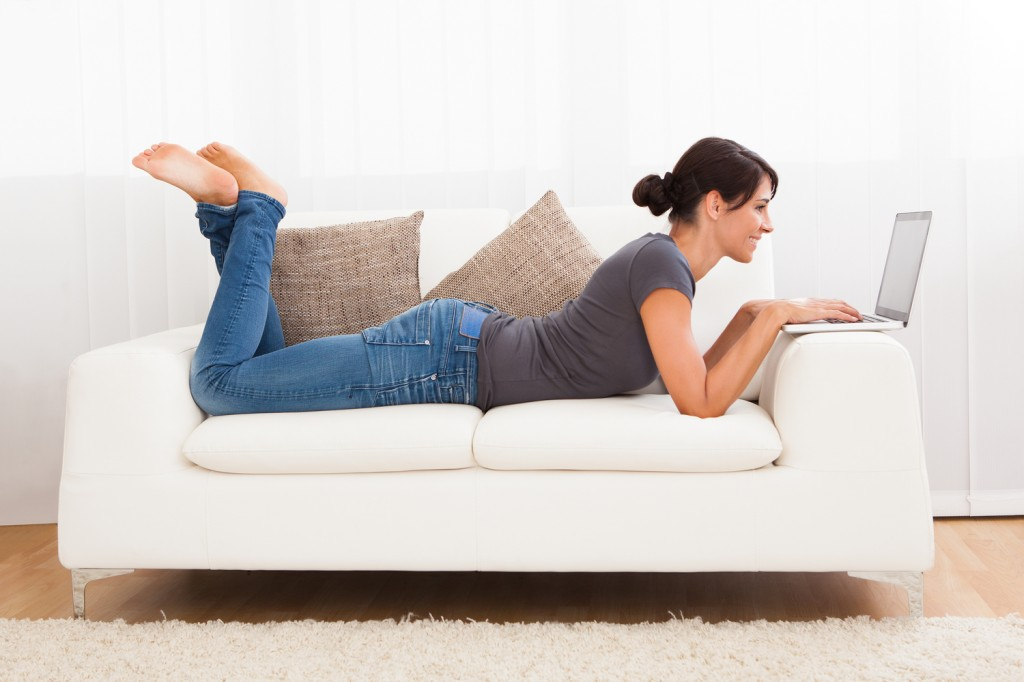 Woman-Laying-on-Couch-with-Computer